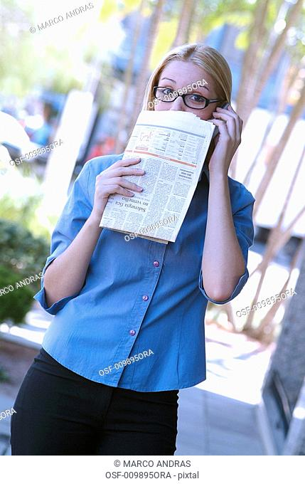 woman hiding her face with newspaper