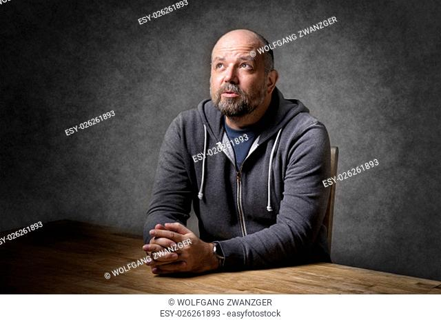 Portrait of a thoughtful looking, balding and unshaven man sitting on a wooden table