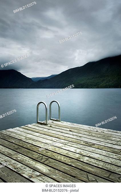Ladder on wooden pier near still remote lake