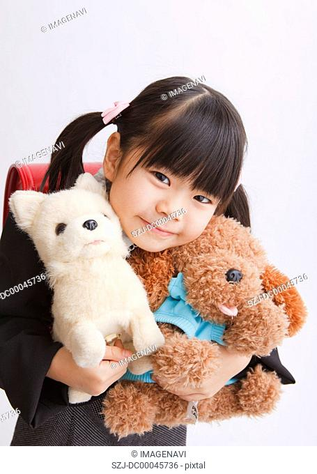 Girl holding stuffed toys