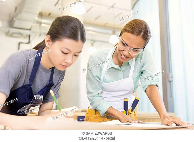 Female carpenters drafting plans in workshop