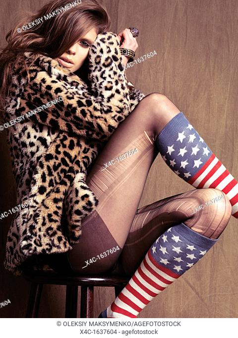 Young woman dressed in 90s grunge fashion style posing on a stool