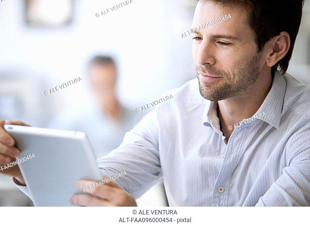 Mid-adult man using digital tablet
