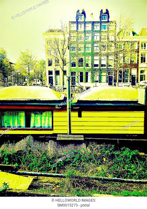 Yellow houseboat moored on canal with typical Dutch architecture, Amsterdam, Netherlands