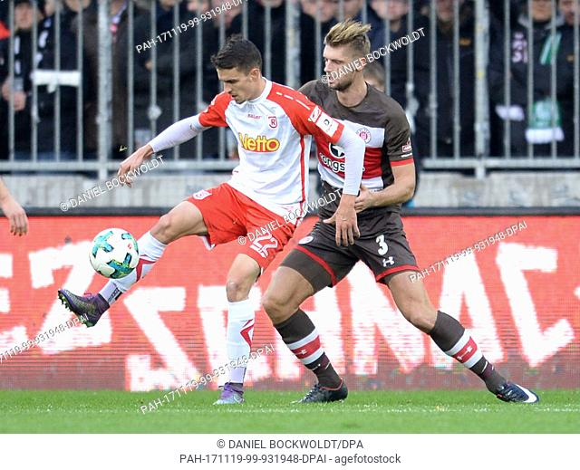 Regensburg's Sebastian Stolze (L) and St. Pauli's Lasse Sobiech vying for the ball during the 2nd Bundesliga soccer match between FC St