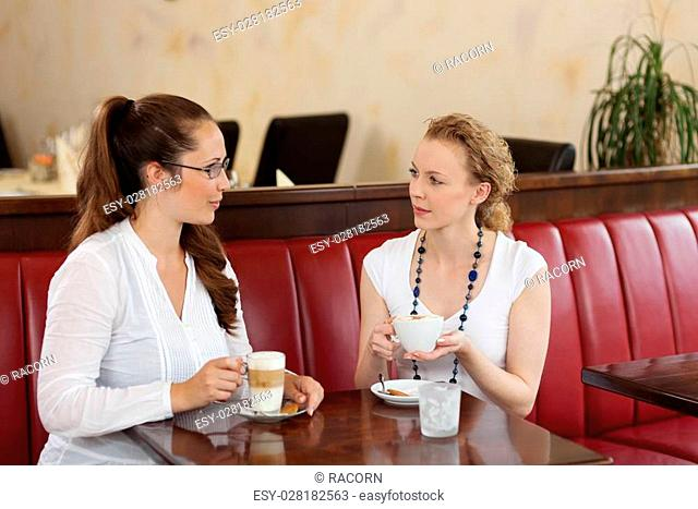 Two stylish beautiful young female friends sitting chatting in a cafe while enjoying cups of coffee