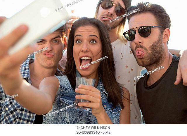 Young adult friends pulling faces for selfie at roof terrace party