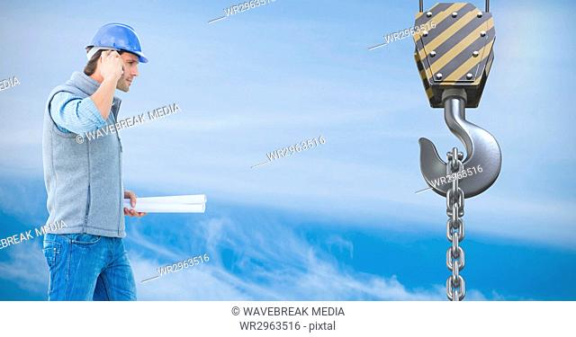 Architect using mobile phone in front of crane hook