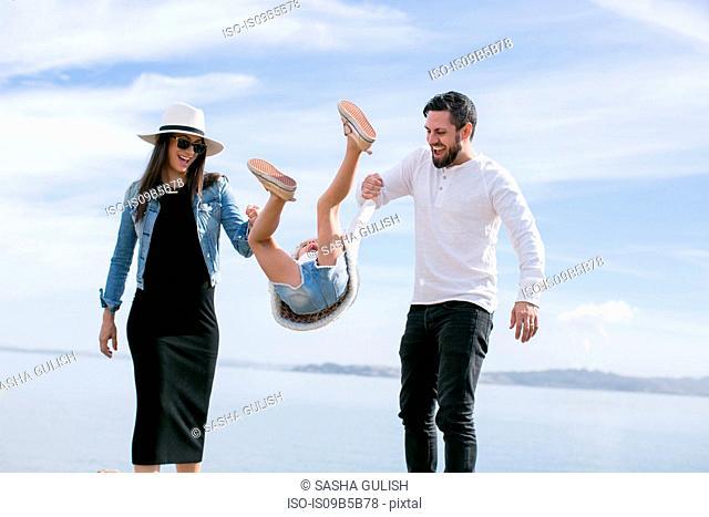 Mature couple swinging daughter at coast