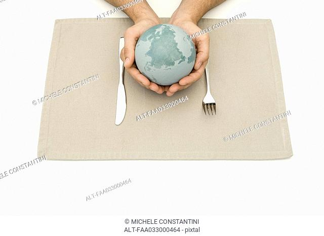 Hands holding globe over placemat and silverware
