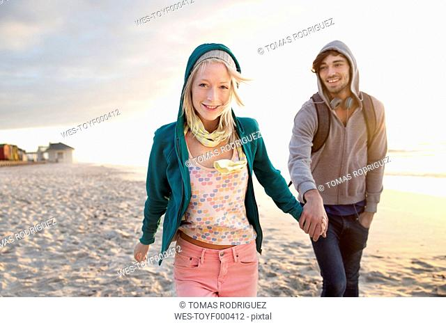 Young couple walking on beach at sunrise