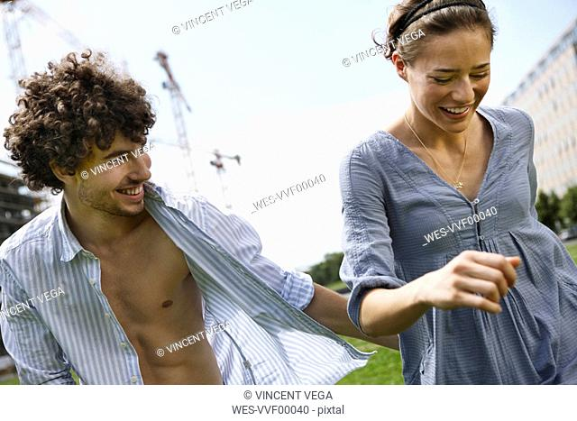 Germany, Berlin, Young couple walking side by side, laughing, portrait