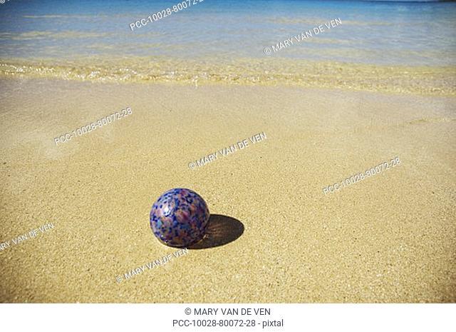 Art glass float on sandy beach with calm ocean