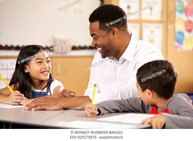 Teacher sitting at desk with two elementary school pupils