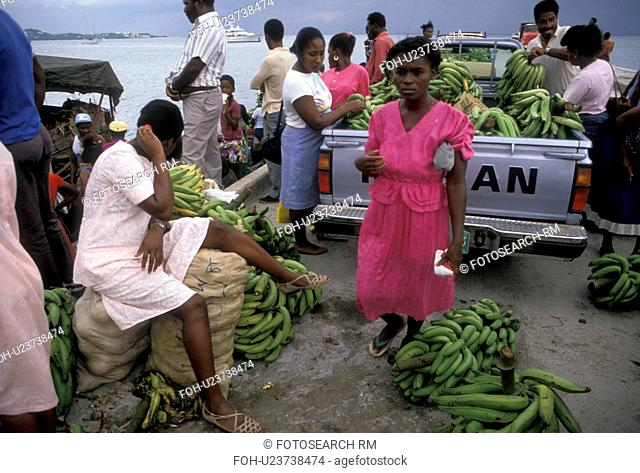 St. Martin, Caribbean, Marigot, Caribbean Islands, Local people loading bananas into pick-up truck from a banana boat in Marigot's harbor the French capital of...