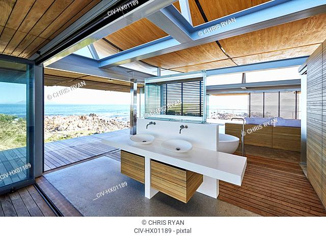 Modern luxury home showcase bathroom open to patio with ocean view