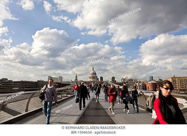 Pedestrians walking across the Millennium Bridge, at the back the cupola of St Paul's Cathedral, London, Great Britain, Europe