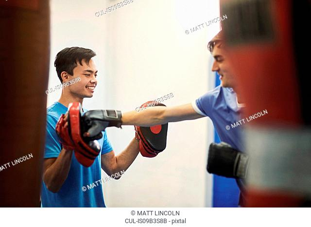 Male boxer training, punching teammate's punch mitt