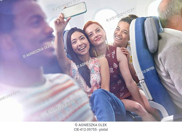 Young women friends with camera phone taking selfie on airplane