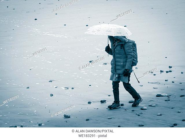 Woman with umbrella walking on beach in the rain