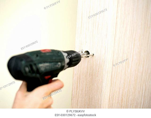 Installation of door lock using a screwdriver to. Carpenter at lock installation with electric drill into wood door