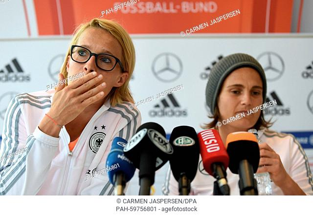 Germany-s Saskia Bartusiak (L) and goalkeeper Nadine Angerer talk during a press conference at the Fairmont Hotel during the FIFA Women-s World Cup in Edmonton