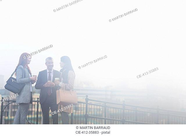 Business people talking and drinking coffee on foggy urban balcony