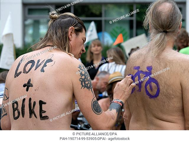 """14 July 2019, Berlin: Danny wears the lettering """"""""Love + Bike"""""""" and Holger paints a purple bicycle on his hairy back during the body painting during the protest..."""