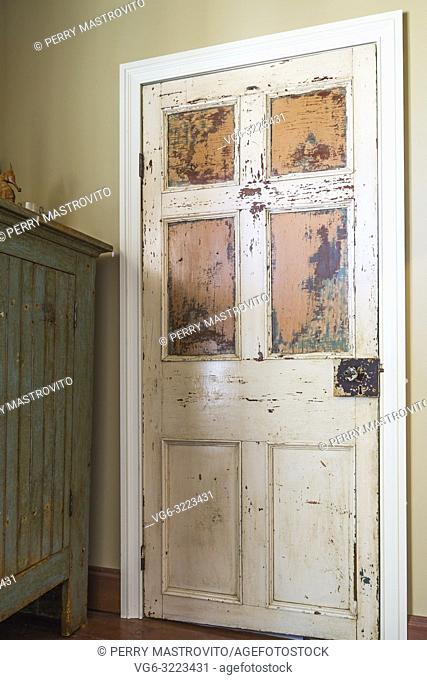 Old wooden closet door with faded white and orange paint in upper floor bedroom inside an old 1835 fieldstone house