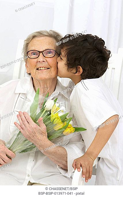 Boy offering flowers to his grandmother