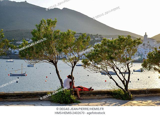Spain, Catalonia, Costa Brava, province of Girona, Cadaques, Avinguda Dr Perez del Pulgar, couples sat on a rail in front of a bay at sunset