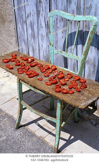 Tomatoes drying on the sun on a old chair in street. Ravanusa, Sicily island, Italy