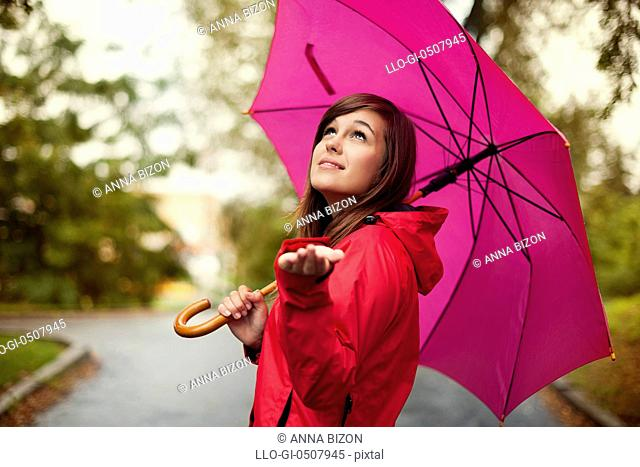 Beautiful woman with umbrella checking for rain, Debica, Poland