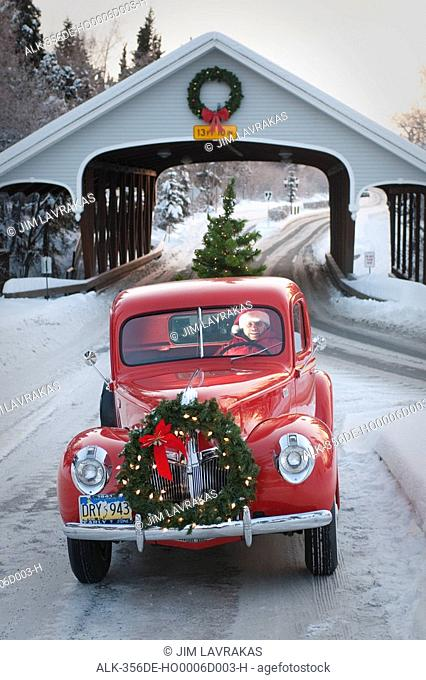 Man driving a vintage 1941 Ford pickup through a covered bridge with a Christmas wreath on the grill and a tree in the back during Winter in Southcentral