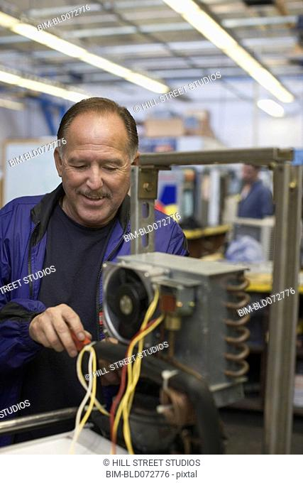 Hispanic refrigeration technician working on equipment