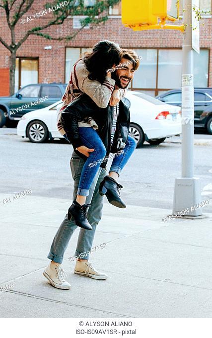 Young woman piggybacking boyfriend on sidewalk, Brooklyn, New York, USA