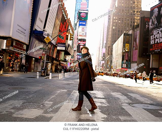 Woman crossing road in Times Square
