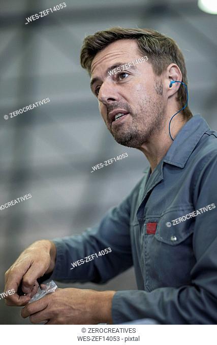 Worker wearing ear plugs in factory