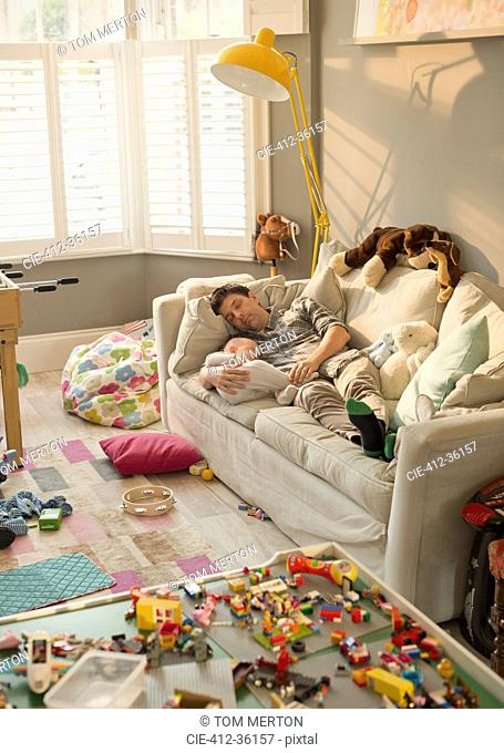 Exhausted father and baby son sleeping on sofa in messy living room with toys