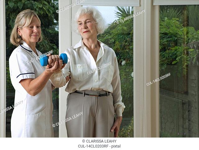Nurse helping woman with exercises