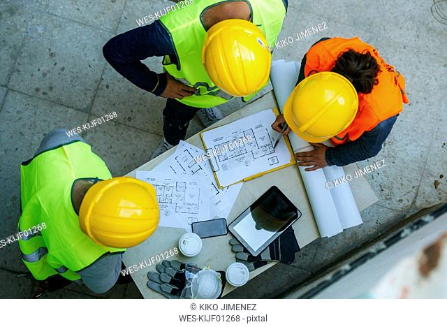 Woman and two men in workwear discussing construction plan