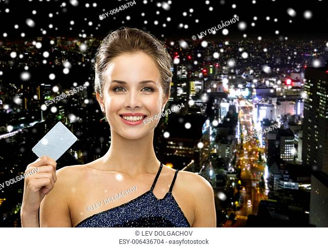 shopping, wealth, money, luxury and people concept - smiling woman in evening dress holding credit card over snowy night city background