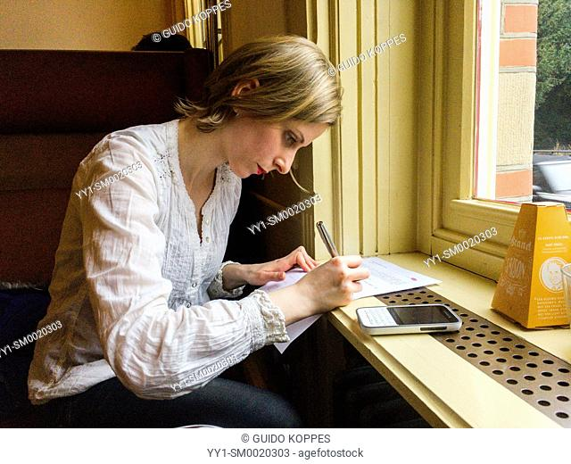 Tilburg, Netherlands. Caucasian woman singning a model release for publication while being photographed inside a cafe