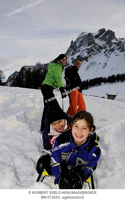 Parents pulling children on a sled on the Pietrarossa Mountain, High Puster Valley or High Puster Valley or Alto Pusteria, Bolzano-Bozen, Italy, Europe