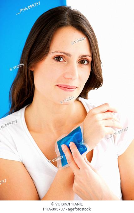 Woman using a hot-cold gel pack treatment to releive pain