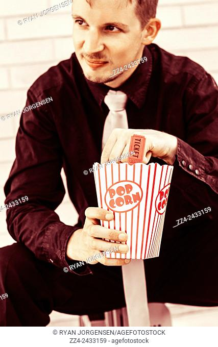 Red toned image of a man eating from a large container of popcorn during a movie theater premiere. Vintage cinema patron