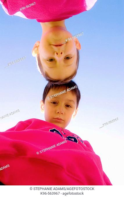 Two boys head to head looking down at camera
