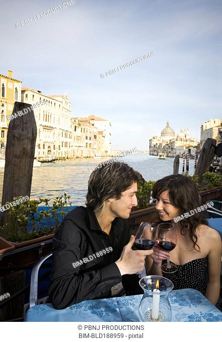 Italian couple drinking red wine at sidewalk cafe