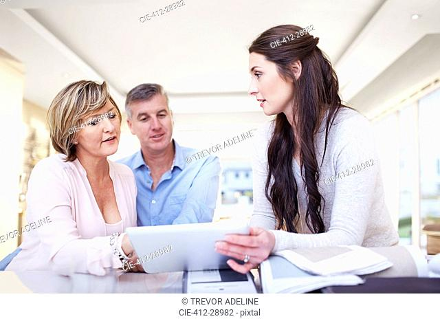 Interior designer using digital tablet in consultation with couple