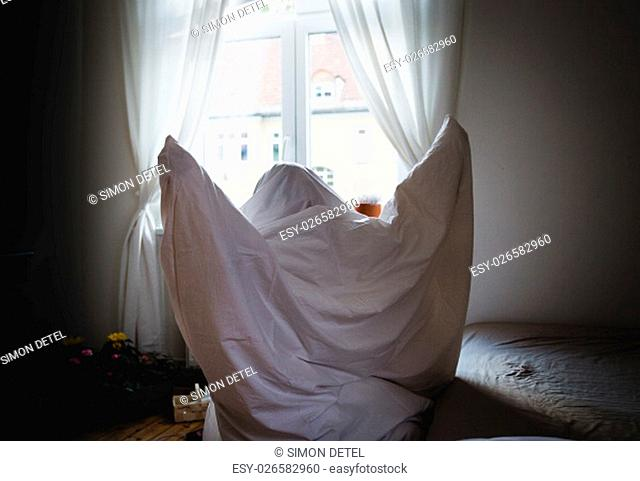 young child dressed in a bed sheets ghost costume for halloween